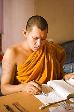 Young Buddhist monk studying, Wat Mahathat, Ko Ratanakosin, Bangkok, Thailand