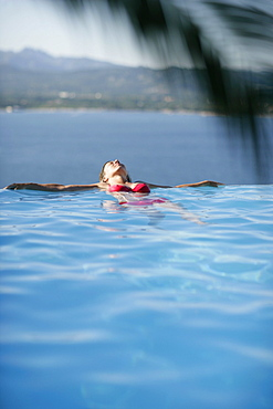 Woman in bikini leaning back in infinity pool, Porto Vecchio, Southern Corse