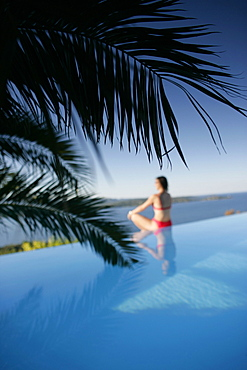 Woman sitting at edge of outdoor pool, sea in back, Bay of Porto Vecchio, Southern Corse, Frankreich