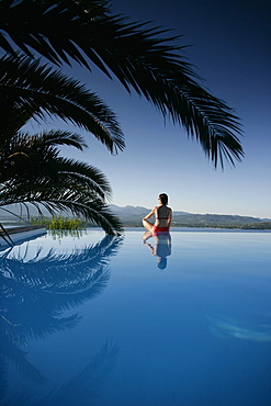 Woman sitting at edge of outdoor pool, sea in back, Bay of Porto Vecchio, Southern Corse, France