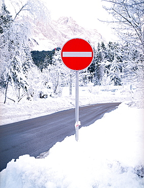 Stop sign in the snow on mountain road, Germany, Bavaria