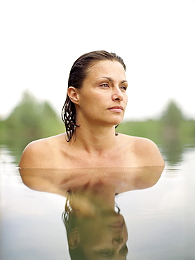 Woman bathing in a lake, mirroring on water surface