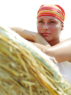 Woman wearing bandanna leaning on a bale of straw looking at view