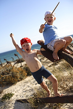 Two boys playing pirates on a rusty anchor at beach, Ilha de Tavira, Tavira, Algarve, Portugal