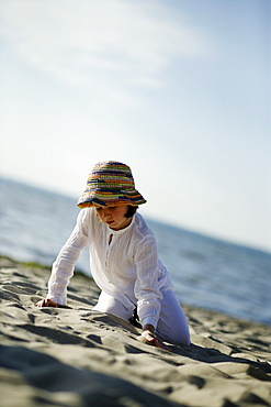 Girl playing at sandy beach, Baltic Sea, Travemuende Bay, Schleswig-Holstein, Germany