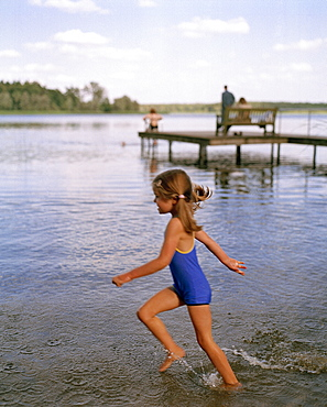 Girl (5 years) walking throug water at lakeshore, Lake Neukloster, Nakenstrof, Mecklenburg-Western Pomerania, Germany, MR, PR
