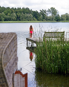 Woman standing on a jetty, Hotel Neuklostersee, Nakenstorf, Mecklenburg-Western Pomerania, Germany