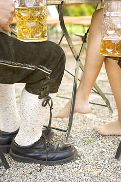 Man's and woman's legs with beer steins in beer garden, Munich, Bavaria