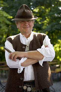 Older Bavarian man with pipe wearing traditional clothes, Munich, Bavaria