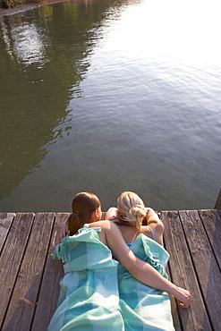 Two young women lying on boardwalk in blanket, Munich, Bavaria