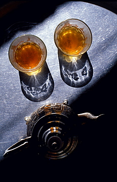 Glasses of tea and a tea pot in a beam of light, Marocco, Africa