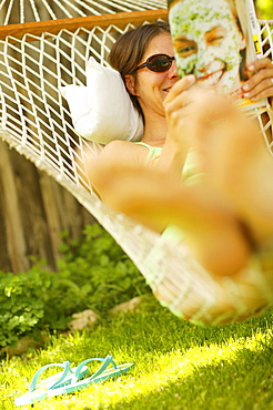 Woman relaxing in a hammock in the garden, reading a magazine, relaxation