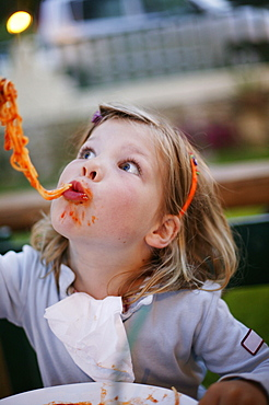 Girl eating spaghetti, pasta sauce on face, side view