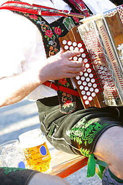 Man wearing traditional leather trousers playing accordion, Garmisch Partenkirchen, Bavaria, Germany