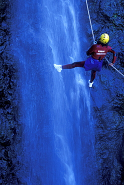 Person canyoning at Gobert Waterfall, Cilaos, La Réunion, Indian Ocean