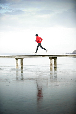 Young man running at jetty
