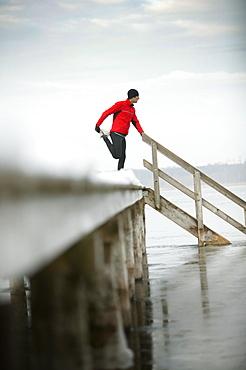Young man streching leg at jetty