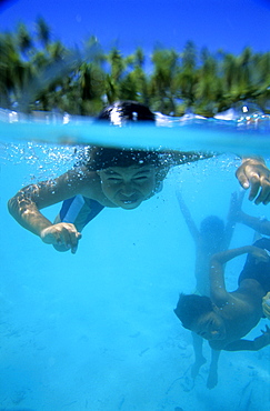 Children swimming under water, diving, Takapotu, Tuamotu Islands, French Polynesia, South Pacific
