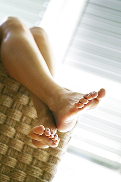 Feet up in cane chair, young woman relaxing