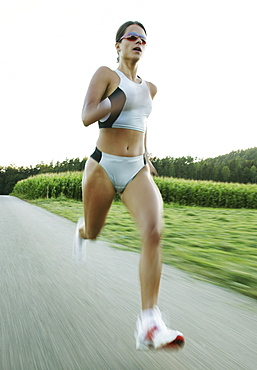 Young woman jogging on country road
