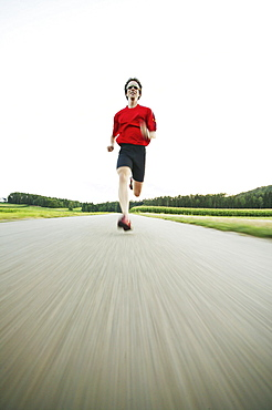 Young man jogging on country road
