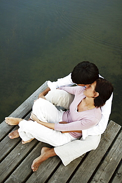 Couple sitting on jetty, man with arms around woman