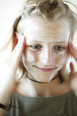 Teenage girl rubbing cream into face