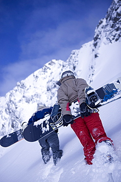 Two people carring snowboards on their back, Kuehtai, Tyrol, Austria