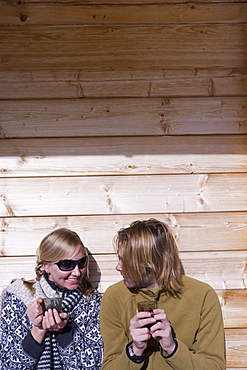 Couple sunbathing on terrace of ski lodge, drinking tea, Kuehtai, Tyrol, Austria