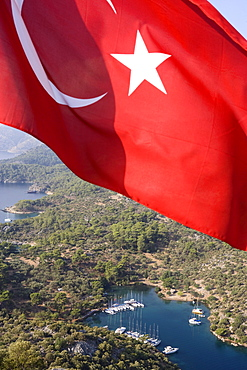 The flag of Turkey in front of the small bay Kapi Creek, Fethiye Bay, Turkey, Europe