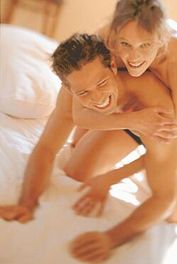 Happy young couple on bed