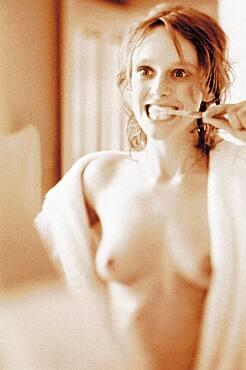 Naked woman brushing teeth