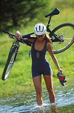Women carring her bike trough water