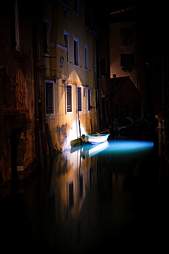 View of a lighted boat and fish in a canal in San Marco at night, Venice, Veneto, Italy, Europe