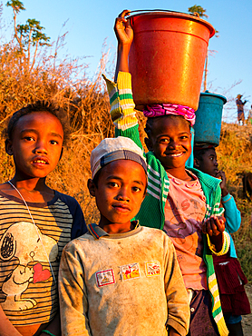 Children come from fetching water, at Ampefy, Merina tribe, highlands, Madagascar, Africa