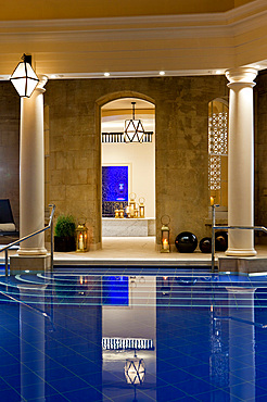 Evening shot of pool room with a view through open door to threatment rooms, Bath, United Kingdom
