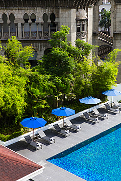 Pool with blue umbrellas, set against an old building and lush greenery. Kuala Lumpur, Malaysia.