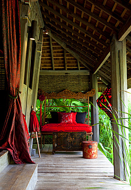 View of terrace of an old Joglo building, decorated with bright, red, Chinese silk. Bali, Indonesia.