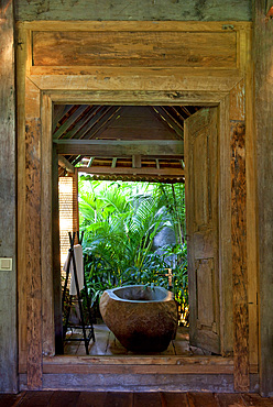 Stone bathtub set inside an open bathroom, in an old wooden house situated in the jungle. Bali, Indonesia.