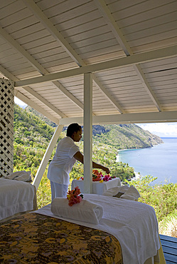 Spa therapist preparing flowers in a white cabana with extended ocean view. St. Lucia, West Indies.