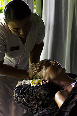 Face massage performed on woman by Balinese therapist. Bali, Indonesia.