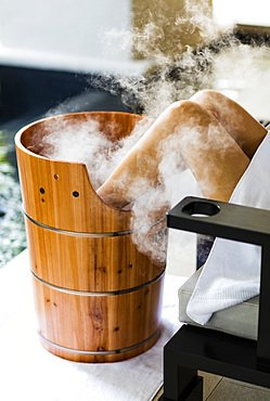 A woman having a footbath, in wooden barrel , with steam billowing. Horizontal. Kuala Lumpur, Malaysia.
