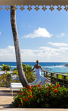 Woman in white, standing on a deck with her back to the camera, looking out onto the ocean. St. Barths.
