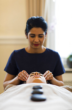 A spa therapist performing a cranial massage, while guest enjoys hot stones on her body. Bath, United Kingdom