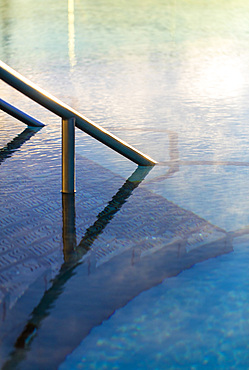 Detail shot of railing going into water in exterior pool, with morning steam. Bath, United Kingdom