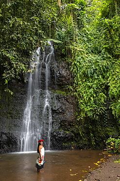 Beautiful young Tahitian woman in front of waterfall in 'The Water Gardens of Vaipahi', Teva I Uta, Tahiti, Windward Islands, French Polynesia, South Pacific