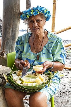 Elderly woman offers pieces of tropical fruit, Hokatu, Ua Huka, Marquesas Islands, French Polynesia, South Pacific