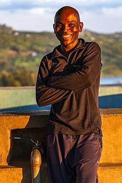 Portrait of a smiling Rwandan man in the late afternoon light, Kinunu, Western Province, Rwanda, Africa