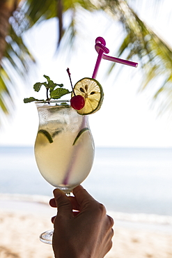 Hand holds cocktail glass with fresh lime juice in the restaurant and bar of the Ancarine Beach Resort on Ong Lang Beach, Ong Lang, Phu Quoc Island, Kien Giang, Vietnam, Asia