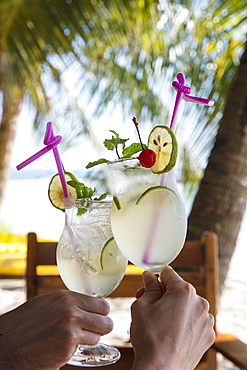 Hands holding two cocktail glasses with fresh lime juice in the restaurant and bar of the Ancarine Beach Resort on Ong Lang Beach, Ong Lang, Phu Quoc Island, Kien Giang, Vietnam, Asia